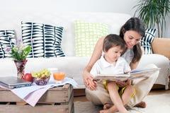 Madre y niño, leyendo un libro y comiendo las frutas Fotos de archivo libres de regalías