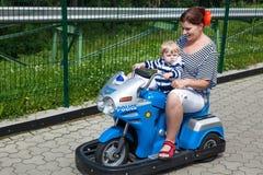 Madre y niño pequeño que juegan junto al aire libre en el coche del juguete Fotografía de archivo