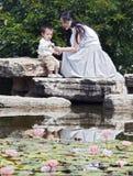 Madre y niño por la charca de loto Fotografía de archivo libre de regalías