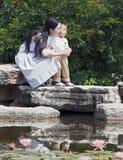 Madre y niño por la charca de loto Imagen de archivo