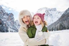 Madre y niño que abrazan al aire libre delante de las montañas nevosas Imagen de archivo libre de regalías