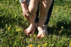 Madre y niño que caminan descalzo en la hierba Foto de archivo