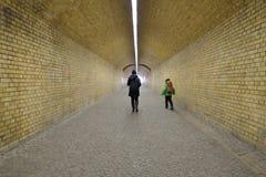 Madre y niño que caminan a través de un paso inferior Imagenes de archivo