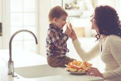 Madre y niño que comen en la cocina Imagenes de archivo