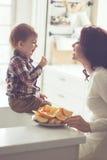 Madre y niño que comen en la cocina Fotos de archivo libres de regalías