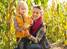 Madre y niño que desvainan maíz en campo de maíz Fotografía de archivo libre de regalías