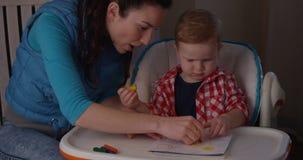 Madre y niño que expresan el dibujo de la creatividad junto metrajes