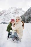 Madre y niño que juegan al aire libre delante de las montañas nevosas Imagenes de archivo