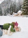 Madre y niño que juegan al aire libre delante de las montañas nevosas Foto de archivo
