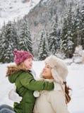 Madre y niño que juegan al aire libre delante de las montañas nevosas Imágenes de archivo libres de regalías