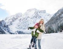 Madre y niño que juegan al aire libre delante de las montañas nevosas Fotos de archivo libres de regalías