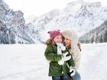 Madre y niño que juegan al aire libre delante de las montañas nevosas Fotografía de archivo