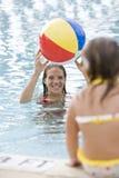 Madre y niño que juegan con la bola de playa en piscina Fotografía de archivo libre de regalías