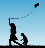 Madre y niño que juegan con la cometa