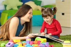 Madre y niño que juegan con un libro imagenes de archivo