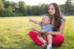 Madre y niño que juegan en la hierba muchacho travieso que llora y y punto por su finger Fotografía de archivo
