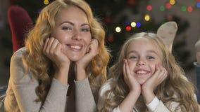 Madre y niño que mienten cerca del árbol de Navidad que sacude las piernas que sonríen en la cámara, celebración almacen de metraje de vídeo
