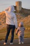 Madre y niño que miran ruinas de la ciudad antigua en puesta del sol Fotografía de archivo libre de regalías