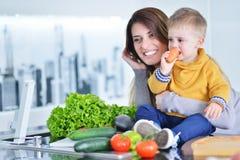 Madre y niño que preparan el almuerzo de los veggies frescos Foto de archivo libre de regalías