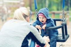Madre y niño que se divierten en el oscilación en el patio fotos de archivo