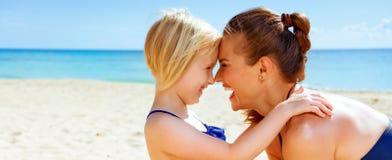 Madre y niño sanos felices en el abarcamiento de la costa Imágenes de archivo libres de regalías