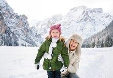 Madre y niño sonrientes al aire libre delante de las montañas nevosas Imagen de archivo