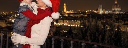Madre y niño sonrientes en sombreros de la Navidad en el abarcamiento de Florencia Fotos de archivo