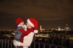 Madre y niño sonrientes en sombreros de la Navidad en el abarcamiento de Florencia Imagen de archivo