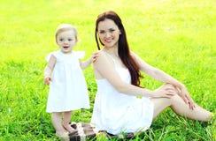 Madre y niño sonrientes felices en la hierba en verano soleado Imágenes de archivo libres de regalías