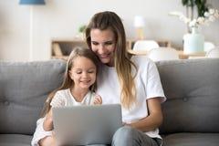 Madre y niño sonrientes que tienen compras divertidas en línea con el ordenador portátil imagen de archivo