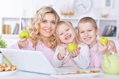 Madre y niños con el ordenador portátil Foto de archivo libre de regalías