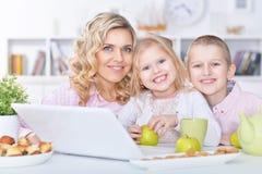 Madre y niños con el ordenador portátil Fotos de archivo libres de regalías
