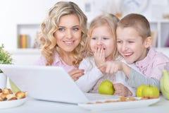 Madre y niños con el ordenador portátil Imágenes de archivo libres de regalías