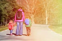 Madre y niños con las mochilas que caminan en el camino Foto de archivo libre de regalías