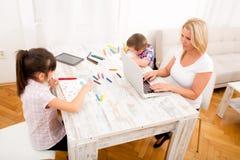 Madre y niños con un ordenador portátil en casa Fotos de archivo