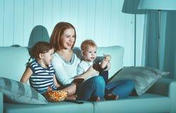 Madre y niños de la familia que miran la televisión en casa Imágenes de archivo libres de regalías