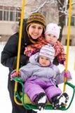 Madre y niños en el oscilación en invierno Imágenes de archivo libres de regalías