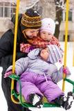 Madre y niños en el oscilación en invierno Fotos de archivo libres de regalías