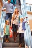 Madre y niños en la escalera móvil en alameda de compras foto de archivo libre de regalías
