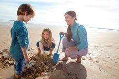 Madre y niños en la excavación de la playa Fotos de archivo libres de regalías