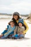 Madre y niños en la playa del invierno Imágenes de archivo libres de regalías