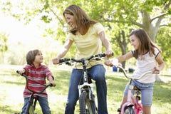 Madre y niños en las bicis fotos de archivo