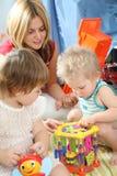 Madre y niños en sala de juegos Imágenes de archivo libres de regalías