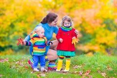 Madre y niños en un parque del otoño Foto de archivo