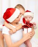 Madre y niños felices de la familia con el regalo en sombreros de la Navidad imagenes de archivo