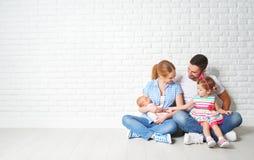 Madre y niños felices del padre de la familia en la pared vacía imagenes de archivo