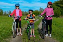 Madre y niños felices en las bicis que completan un ciclo al aire libre Foto de archivo libre de regalías