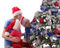 Madre y niños felices sobre el árbol de navidad Foto de archivo libre de regalías
