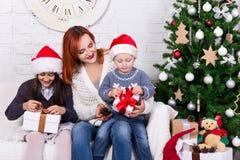 Madre y niños jovenes con las cajas de regalo delante de Christm fotografía de archivo libre de regalías