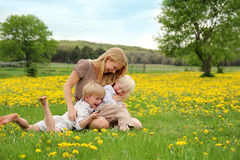 Madre y niños jovenes que se sientan en la risa del prado de la flor Imágenes de archivo libres de regalías